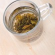 Green tea in glass cup with leafs on board — Stock Photo