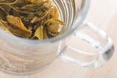 Green tea in glass cup with leafs, macro — Stock Photo