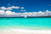 Beach with sailboat in ocean — Stock Photo