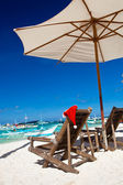 Sun umbrella with Santa Claus Hat on chairs — Stock Photo