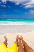 Male and female legs on tropical beach — Stock Photo