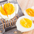 Egg cutter and cutted eggs on wooden table — Stock Photo #23140298