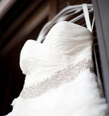 White wedding dress hanging on a shoulders — Stock Photo