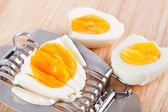 Egg cutter and cutted eggs on wooden table — Stock Photo