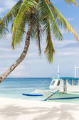 Wooden boat on tropical beach — Stock Photo