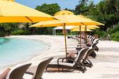Sun umbrellas and beach chairs on tropical beach — Stock Photo