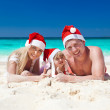 Happy family on beach in Santa hats, celebration christmas — Stock Photo