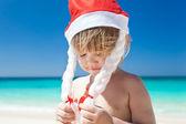 Сute little girl in Santa hat on beach — Stockfoto