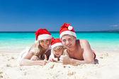 Happy family on beach in Santa hats, celebration christmas — Stock Photo