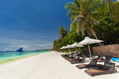 Sun umbrellas and beach chairs on tropical coastline — Stock Photo