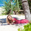 Blond girl with a laptop on tropical beach — Stock Photo