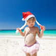 Сute little girl in Santa hat on beach — Stock Photo