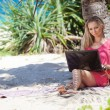 Blond girl with a laptop on tropical beach — Stock Photo #33764927