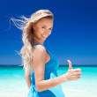 Happy blond girl on beach, showing okey sign — Stock Photo #34252033