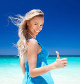 Happy blond girl on beach, showing okey sign — Stock Photo