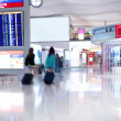 Walking passengers with baggage in airport — Stock Photo