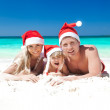 Happy family celebrating Christmas on beach — Stockfoto