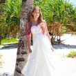 Tropical wedding, bride near palm tree — Stock Photo