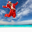 Santa Claus jumps on tropical beach — Stock Photo