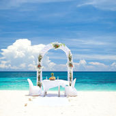 Beautiful wedding arch on tropical beach — Stock Photo