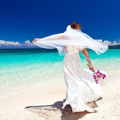 Happy dancing bride on beach in wedding dress — Stock Photo