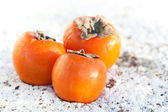 Delicious persimmons on white snow — Stock Photo