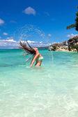 Woman in ocean waving and splashing water — Stock Photo