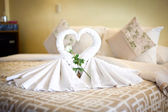 View of two white towels swans on bed sheet in hotel — Photo