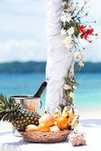 Beautiful wedding arch on tropical beach, focus on bottle — Stock Photo