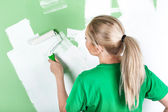 Woman paints the wall — Stock Photo