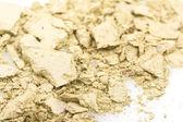 Crushed yellow eyeshadows on white background — Stock Photo