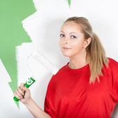 Young woman with paint roller in hand — Stock Photo