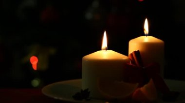 Flame of candle on  blinking christmas lights — Stock video
