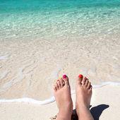 Woman legs lying on sandy beach — Stock Photo