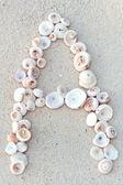 буквы, сделанные из ракушки на песке — Стоковое фото