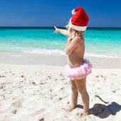Cute little girl in Santa hat on beach — Stock Photo