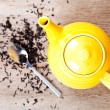 Yellow teapot with spoon and tea — Stock Photo #12782591