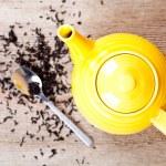 Yellow teapot with spoon and tea — Stock Photo