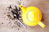 Yellow teapot with spoon and tea — Stock Photo