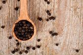 Black peper in wooden spoon — Stock Photo