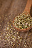 Dry oregano in wooden spoon — Stock Photo