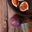 Fresh figs in a plate, old knife and towel - Stock Photo