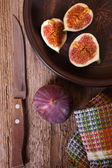 Fresh figs in a plate, old knife and towel — Stock Photo