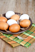 Eggs in a plate, towel and feathers — Stock Photo