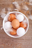 Eggs and feathers on wooden table — Stock Photo