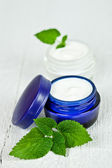 Face cream in jars with urtica leaves — Stock Photo
