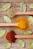 Three spices in wooden spoons and bay leaves — Stock Photo