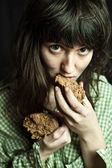 Beggar woman eating bread — Stock Photo