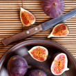 plate with fresh figs and old knife on straw background — Stock Photo