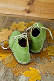 Pair of green leather boots and yellow leaves — Stock Photo